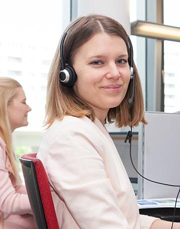 1450-Mitarbeiterin mit Headset an ihrem Arbeitsplatz