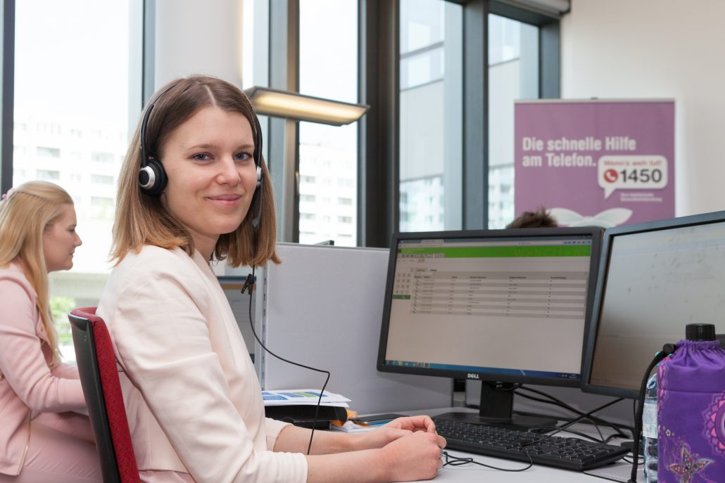 Mitarbeiterin der telefonischen Gesundheitsberatung sitzt am Arbeitsplatz vor einem PC und blickt direkt in die Kamera